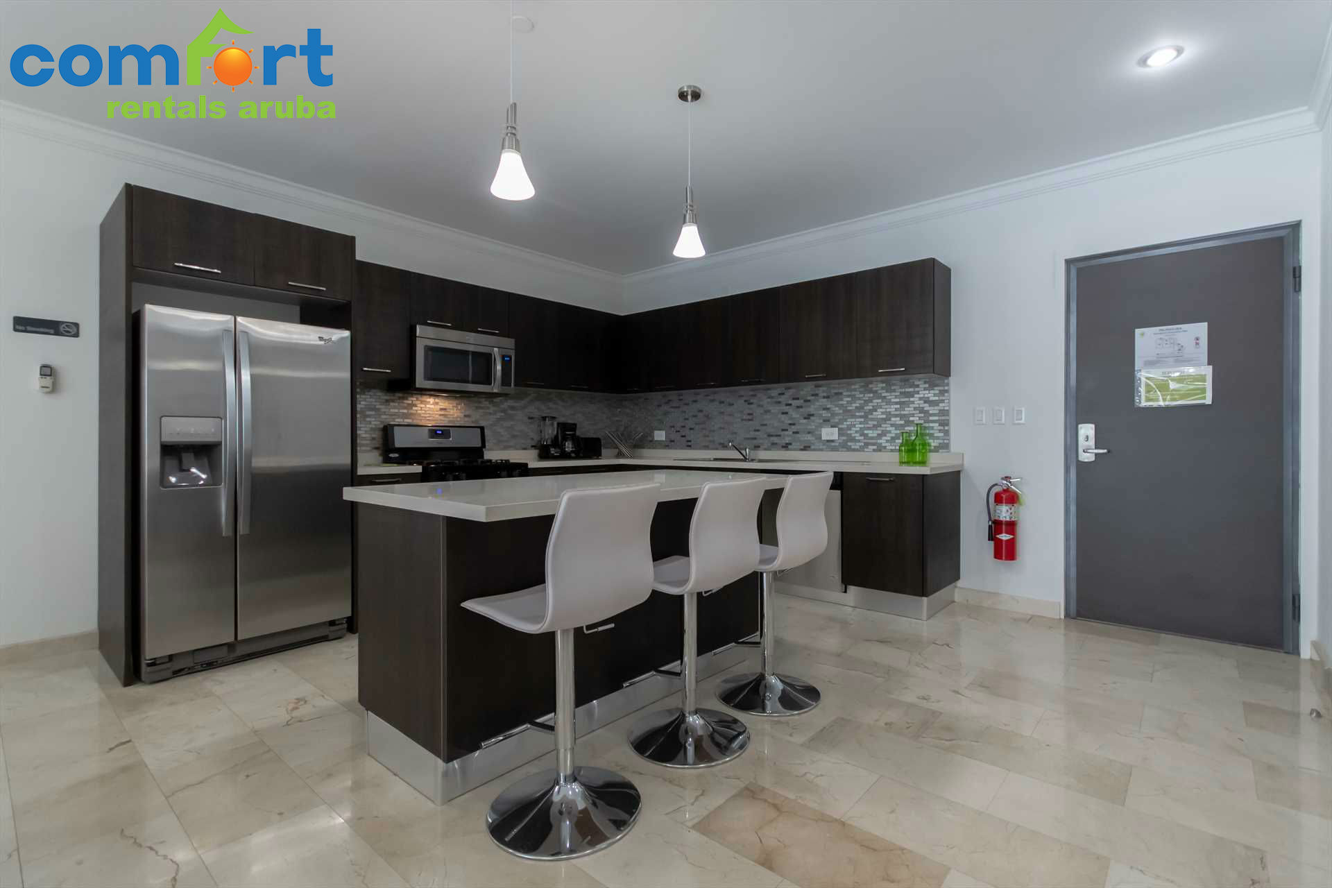 The spacious fully equipped open kitchen and bar-chairs